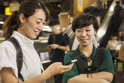 Two smiling women looking at mobile phone