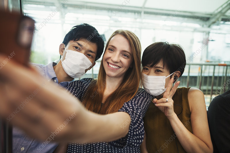 Three people, two with dust masks, selfie, subway platform