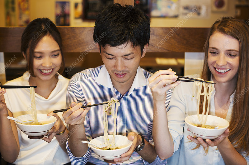 Three smiling people eating at table, bowls, chopsticks