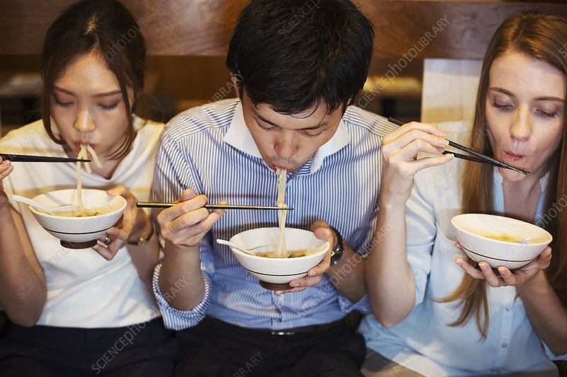 Three people at restaurant table, eating, bowls, chopsticks