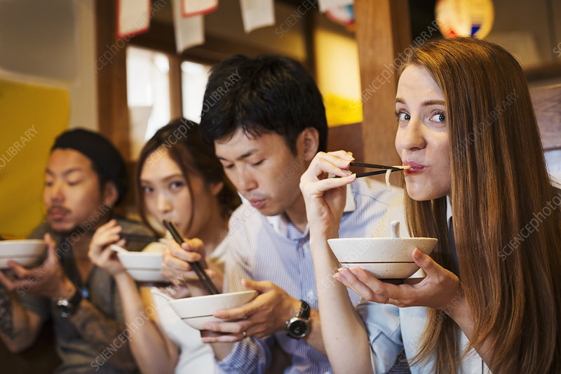 Four people eating at restaurant table, bowls, chopsticks