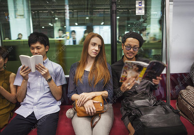 Three people reading on subway train, Tokyo commuters