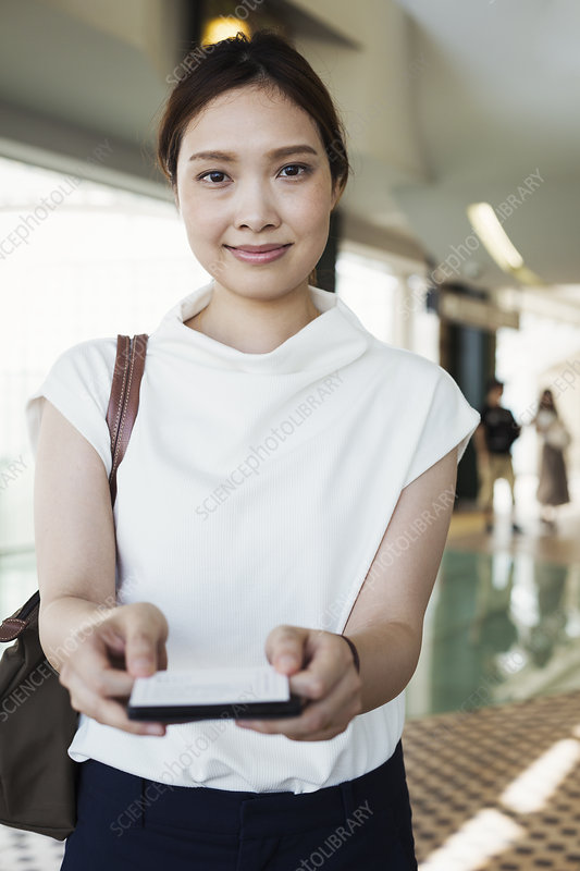 Woman holding ticket, subway station, Tokyo commuter