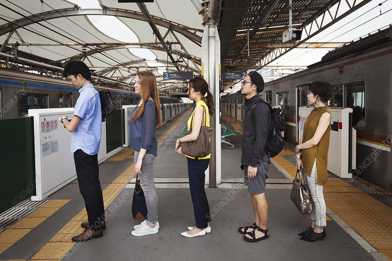 Five people in line on subway platform, Tokyo commuters