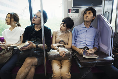 Four people sitting on a subway train, Tokyo commuters