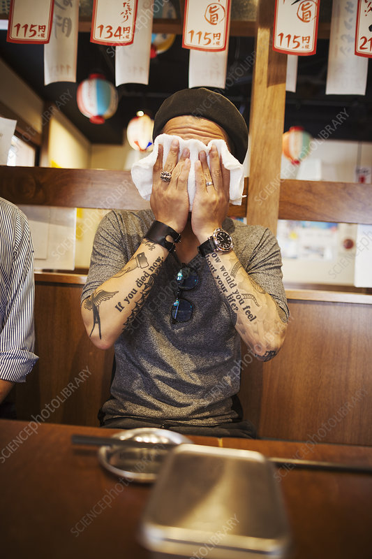 Man wiping face, wet towel, restaurant table, tattooed arms