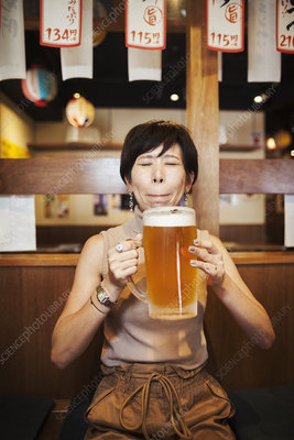 Woman at table in restaurant, holding large glass of beer