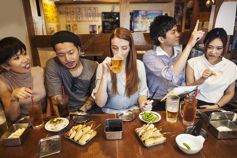Five people at restaurant table, eating and drinking beer