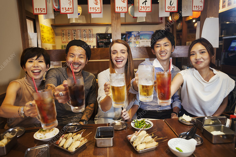 Five people at restaurant table, soft drinks, beer