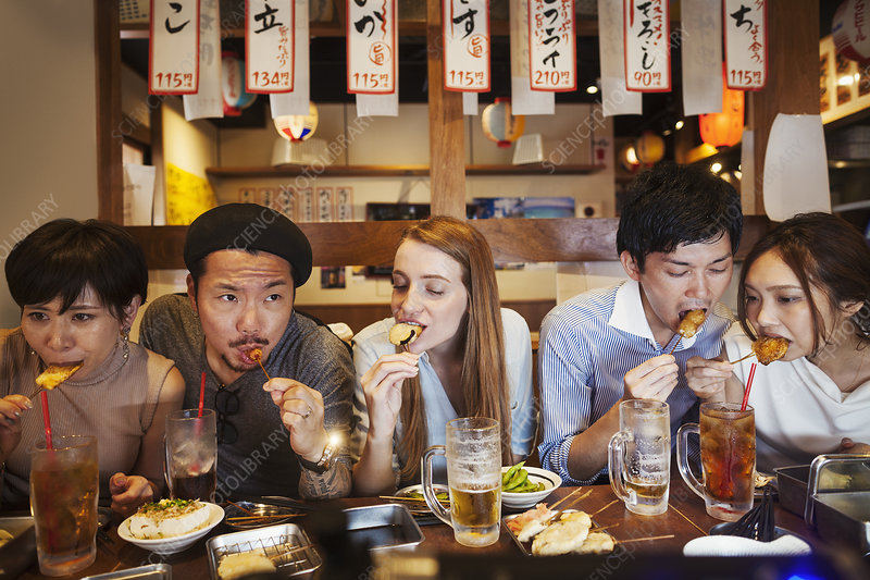 Five people at restaurant table, eating from skewers
