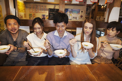 Five people eating at restaurant table, bowls, chopsticks