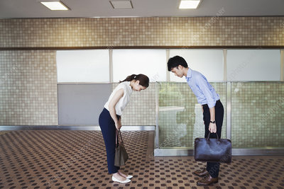 Man, young woman greeting in subway, bowing from waist