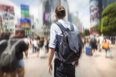 Young man, backpack, crowded street, downtown Tokyo