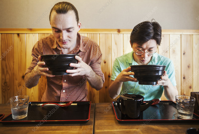 Two people in a noodle cafe lifting bowls of soba noodles