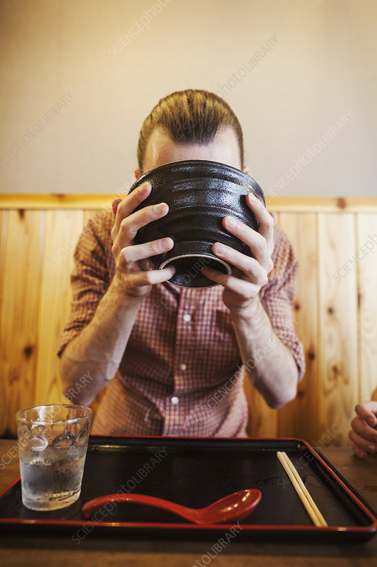 Western man drinking from noodle bowl, noodle restaurant