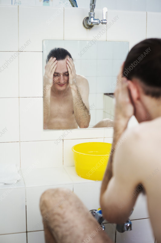 A man washing his face in a bathhouse, view in a mirror
