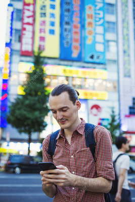Tourist in Tokyo city holding a smart phone