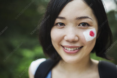 Young woman with Japanese flag painted on her cheek