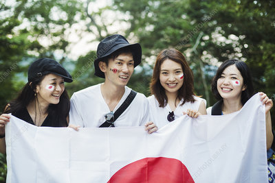 Four young people with painted faces holding Japanese flag