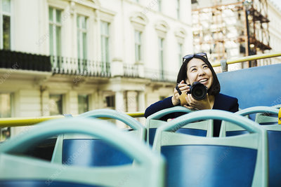 Woman on a tourist sightseeing bus, with a camera