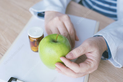 Doctor advising apple instead of pills