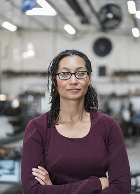 Woman standing in metal workshop, smiling