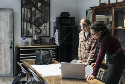 Two women looking at a laptop in a metal workshop