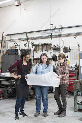 Three women workers standing in metal workshop
