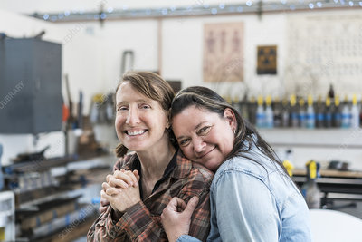 Two women standing in metal workshop