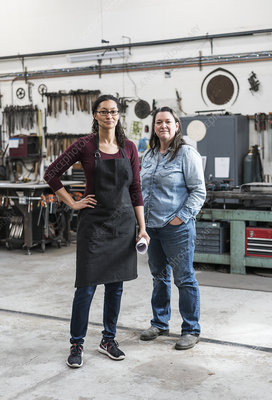 Two women working, smiling at camera