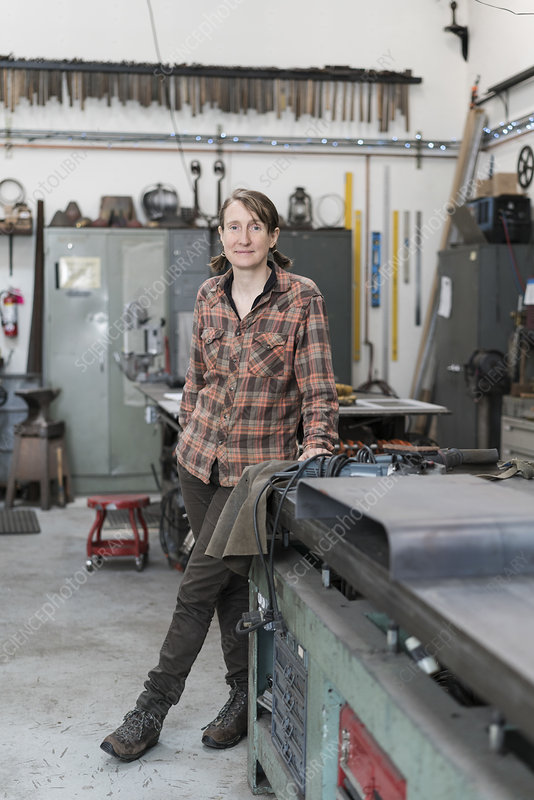 Woman in metal workshop, looking at camera