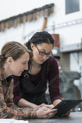 Two women in a workshop looking at digital tablet