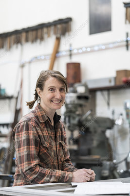 Woman in metal workshop, smiling at camera
