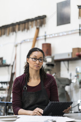 Woman wearing glasses and apron at workbench