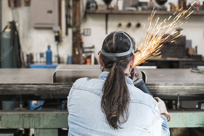 Woman wearing safety glasses using power grinder
