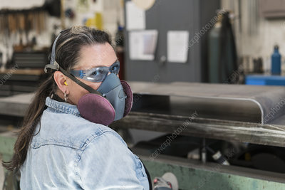 Woman wearing safety glasses and dust mask