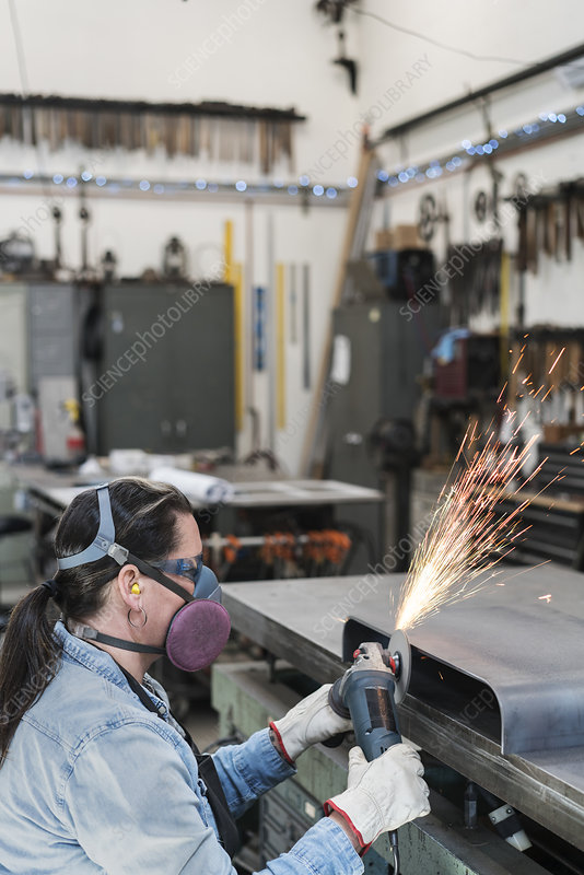 Woman in a metal shop using a power grinder