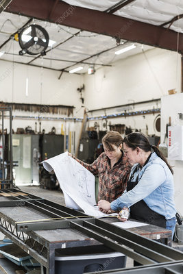 Two women in a metal shop looking at a blueprint