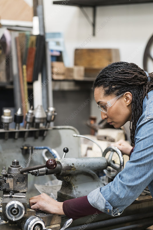 Woman in a metal workshop, working at a machine