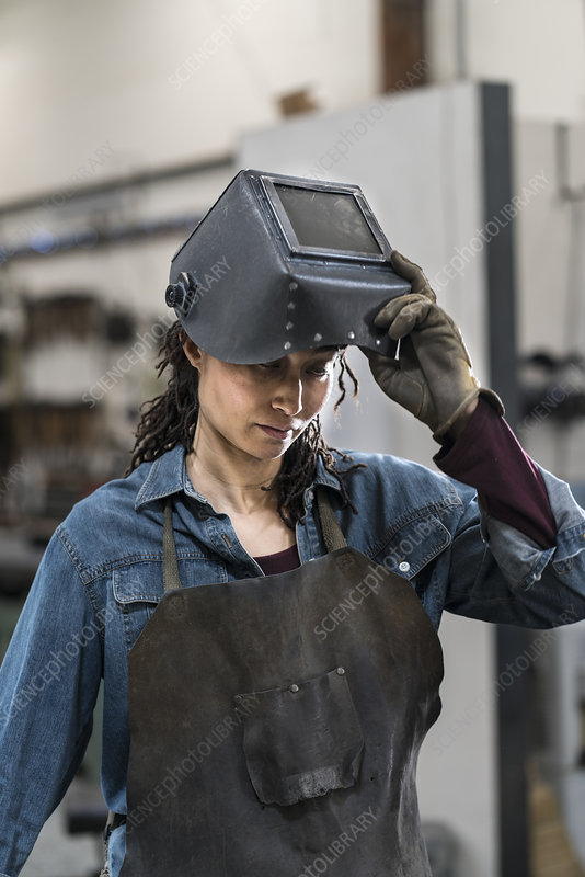 Woman in apron and welding mask standing