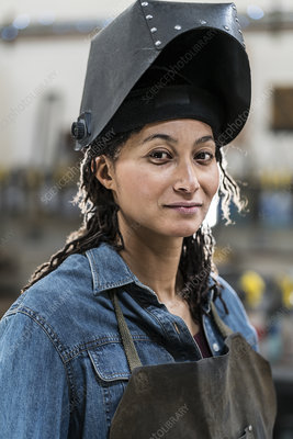 Woman wearing apron and welding mask