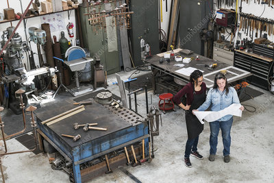 Two women studying a technical blueprint