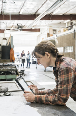 Woman at workbench holding digital tablet
