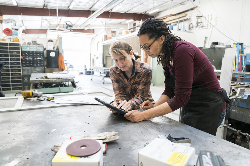 Two women at a workbench using a digital tablet