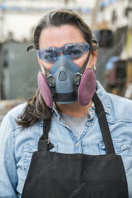 Woman in safety glasses and dust mask