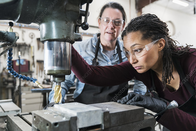 Two women working on metal drilling machine