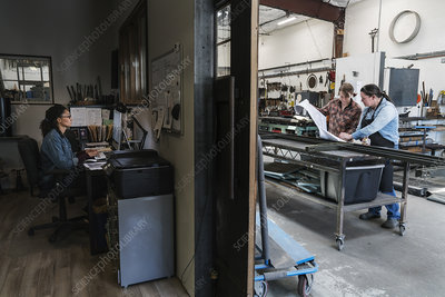 Three women working in a metal workshop