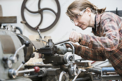 Woman in goggles working at metal lathe machine
