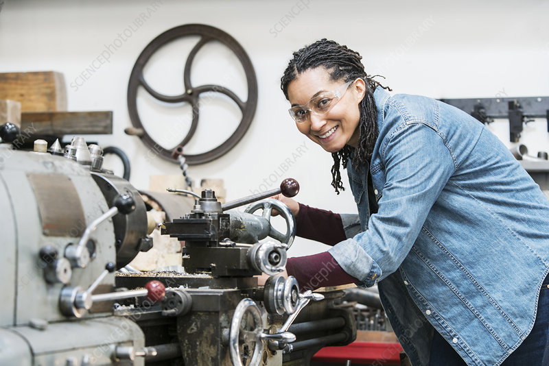 Woman in safety glasses at a machine