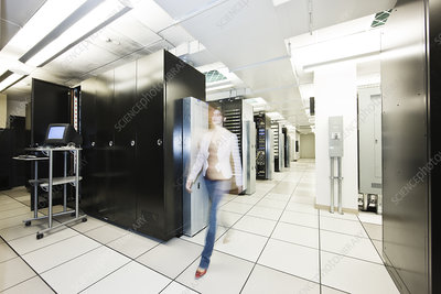 Server room racks with technician in background